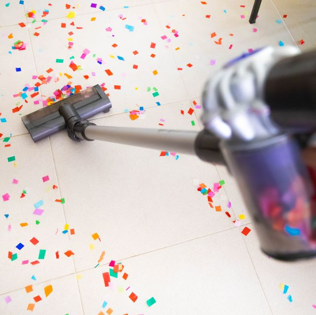 cleaning home floor with vacuum after party with confetti