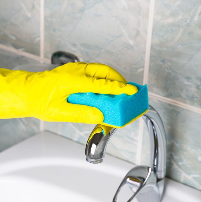 disinfection man in yellow gloves cleans bathroom tap and the bath and sink maid in yellow protective gloves washing dirty bath tap or sink hands of man wash or cleans up bath close up