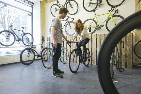 Client testing racing cycle in a custom-made bicycle store