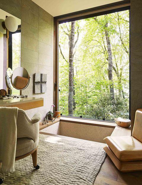 bathroom with sunken tub and window overlooking wooded area