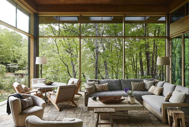 sitting area with sofa chairs and table overlooking wooded area
