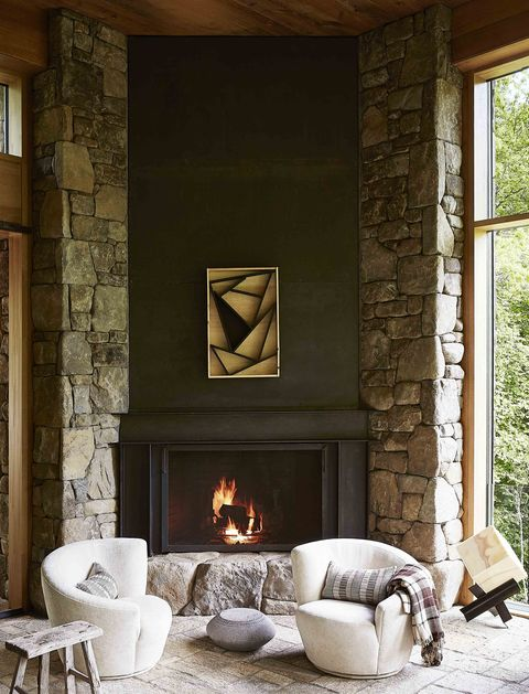 two chairs in front of a stone fireplace