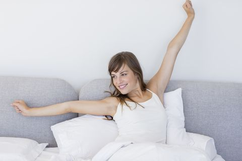 Happy sleepy woman waking up and yawning with a stretch while sitting in bed