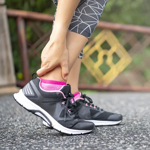 Close-up Asian woman standing on road holds her ankle injury after jogging