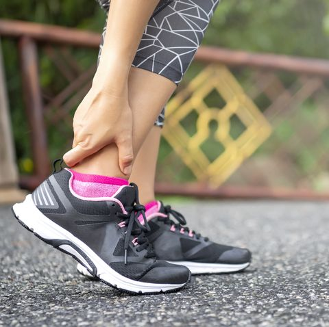 close up asian woman standing on road holds her ankle injury after jogging