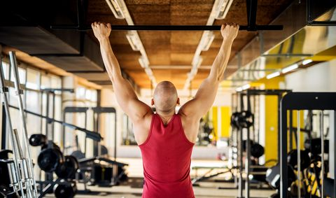 Close up back view of motivated and focused strong muscular active healthy young bald man working pull ups in the modern gym.