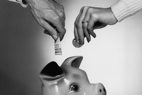 CLOSE-UP COUPLE PLACING MONEY IN PIGGY BANK