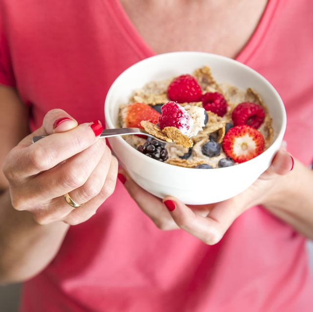 close up crop of woman holding a bowl containing homemade granola or muesli with oat flakes, corn flakes, dried fruits with fresh berries healthy breakfast