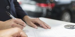 Close up Kunde unterzeichnen Finanzvertrag Papierkram in Autohaus