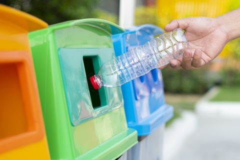 Concept recycly:close up hand throwing empty plastic bottle into the trash recycling.