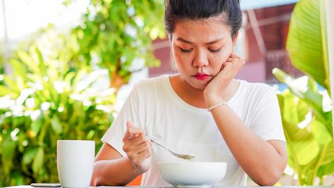 close up head shot of young asian woman hand on chin with bored feeling while eating breakfast in the morning at garden outside home , unhealthy living lifestyle concept