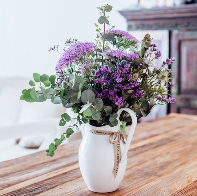 Close-up image of vase with lilac flowers on a wooden table (indoors)