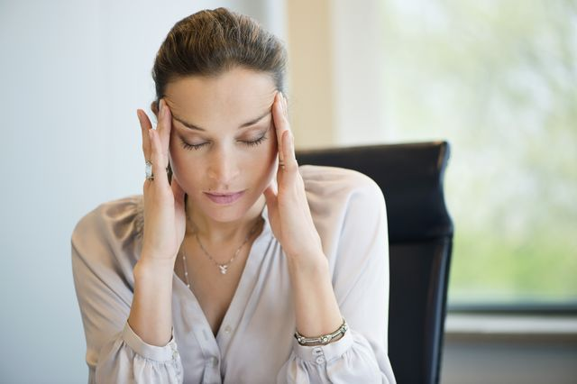 close up of a businesswoman suffering from a headache in an office