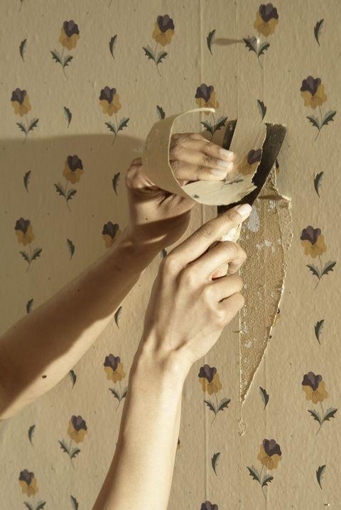 Close up of a hand scraping away wallpaper