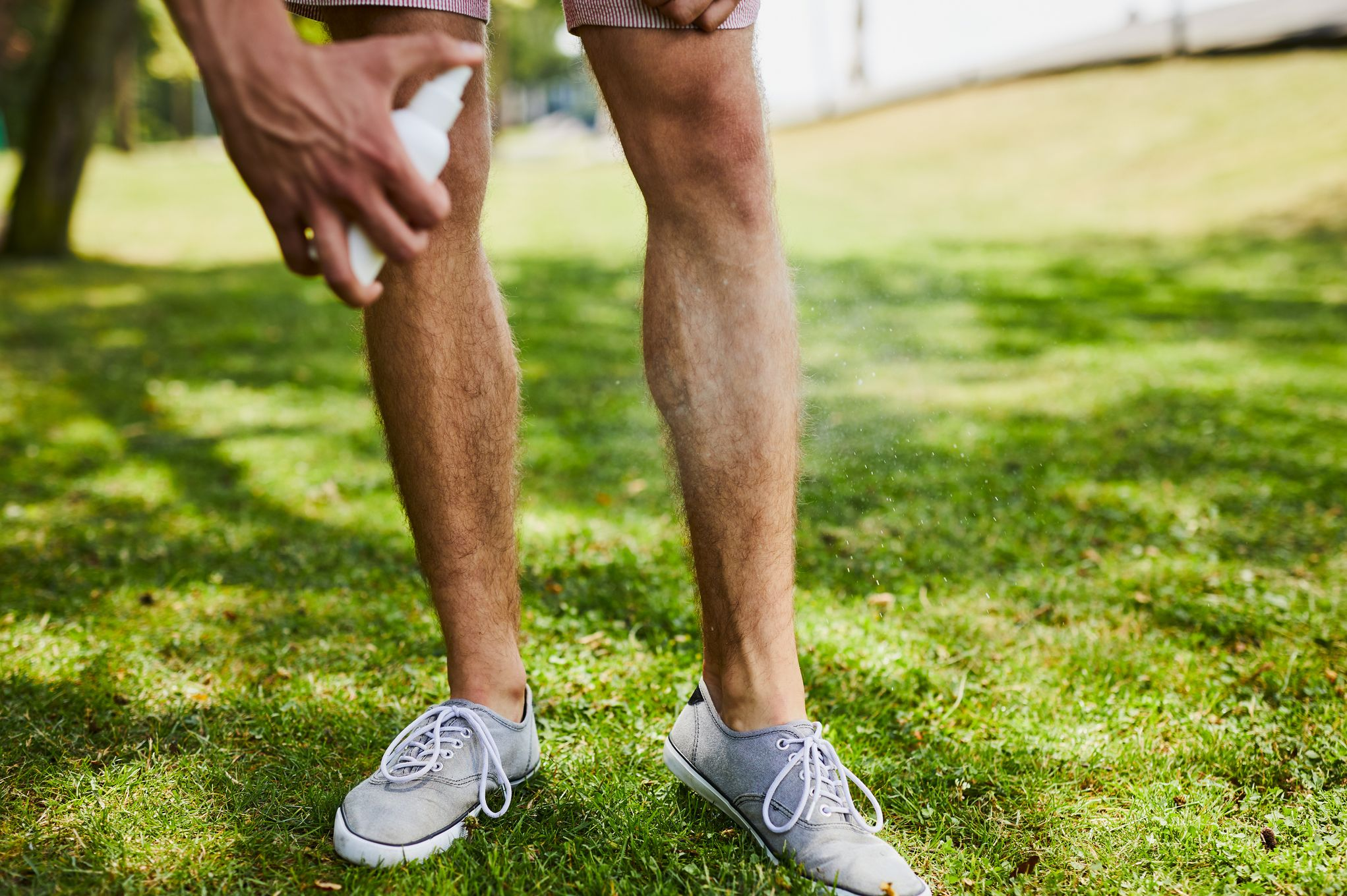Close-up of a man spraying insect repellent on his legs while outdoors