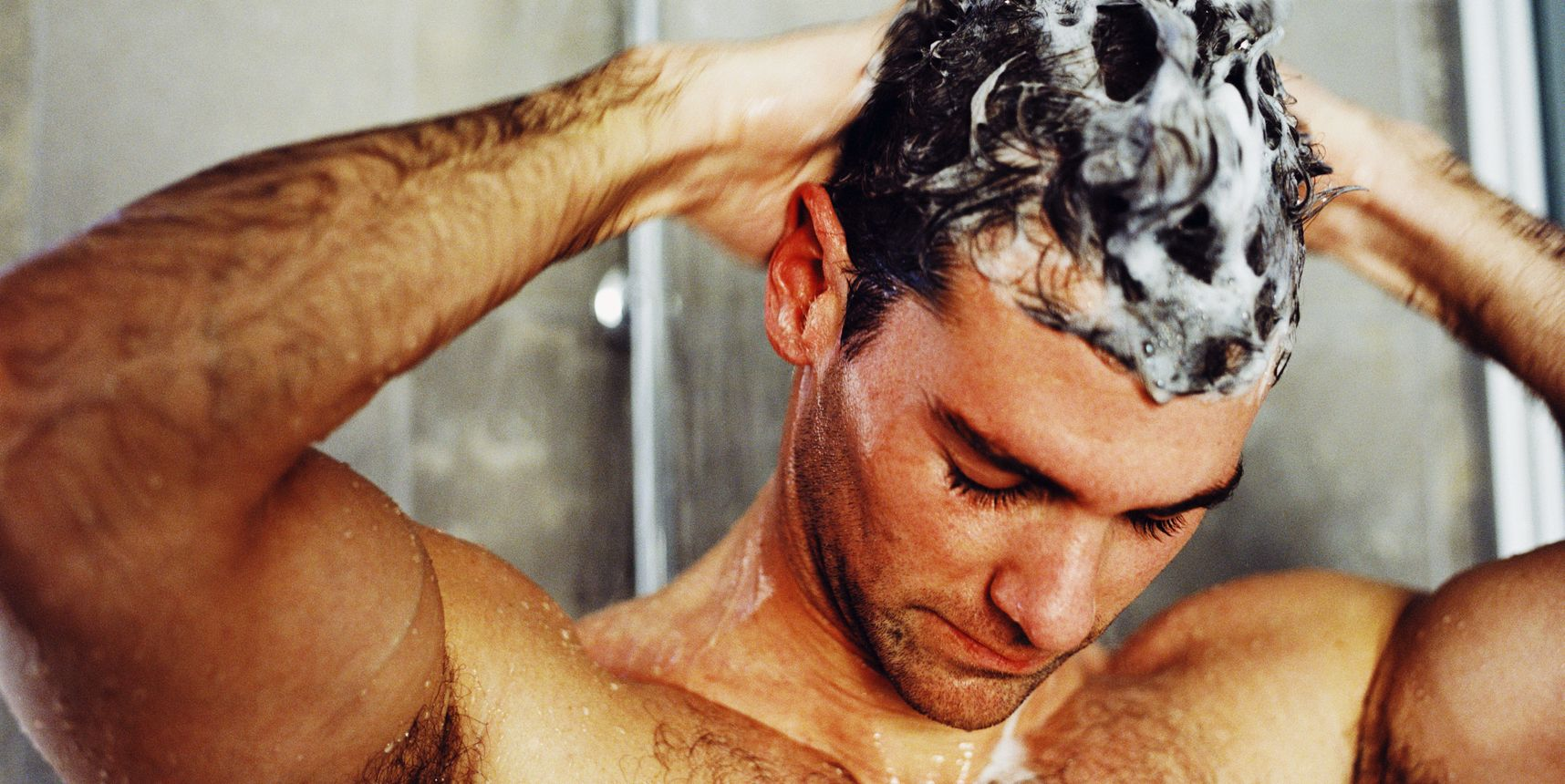 close-up of a man washing his hair in the shower