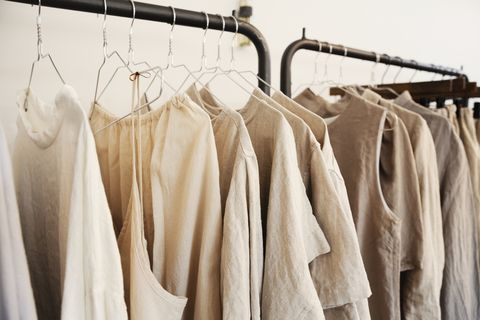 close up of a selection of clothes in natural colours on a rail in a boutique