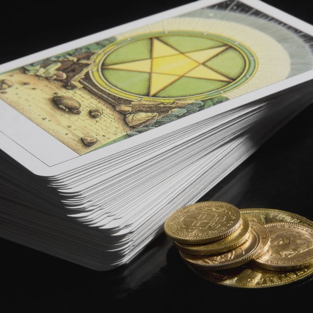 close up of a stack of tarot cards with coins