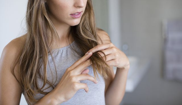 close up of a woman adjusting her hair