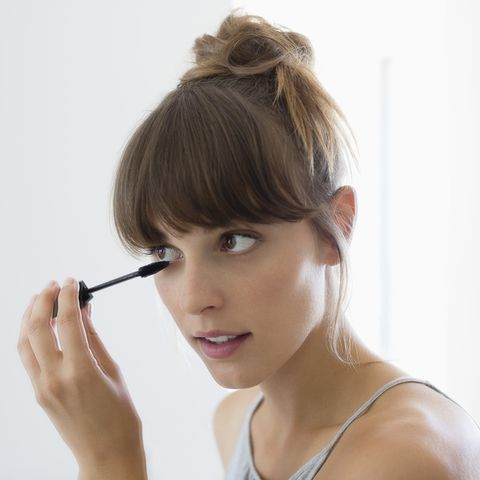 close up of a woman applying mascara