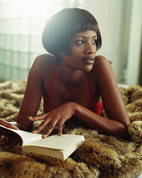close up of a woman lying on a bed and reading a book