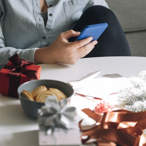 close up of a woman using her smartphone to send messages in a christmas setting