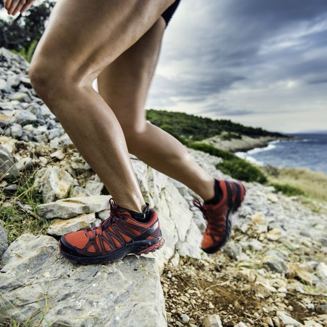 close up of a woman's legs running up a rocky hill