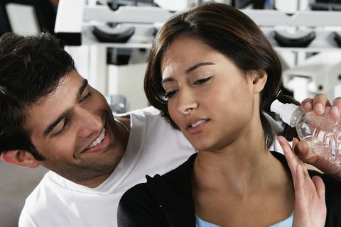 close up of a young man offering a bottle to a young woman in a gym