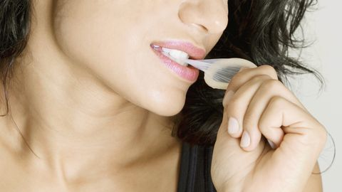 Close-up of a young woman biting a condom