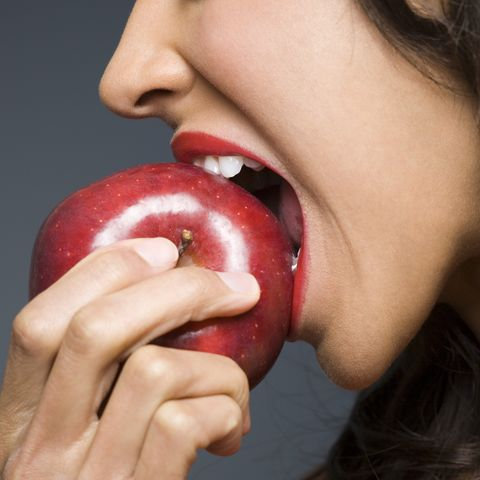 Close-up of a young woman biting an apple