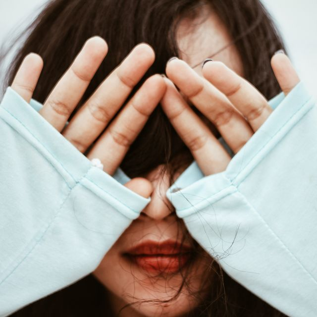 close up of a young woman covering eyes