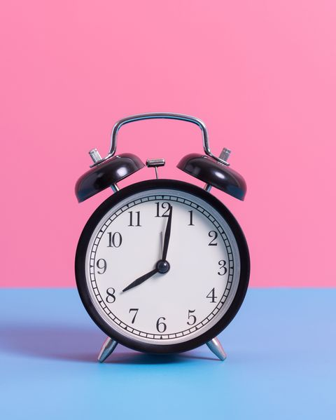 Close-Up Of Alarm Clock On Blue Table Against Pink Wall
