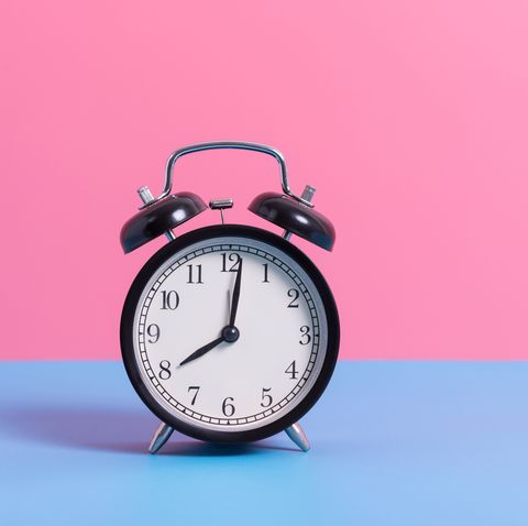 close up of alarm clock on blue table against pink wall
