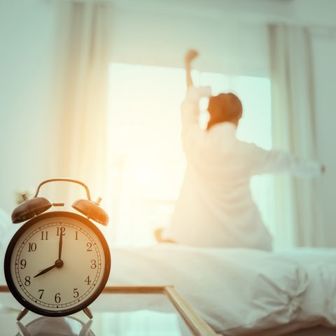 Close-Up Of Alarm Clock On Table Against Woman Sitting On Bed At Home