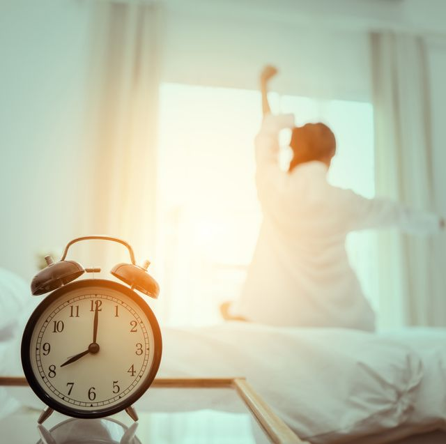 close up of alarm clock on table against woman sitting on bed at home