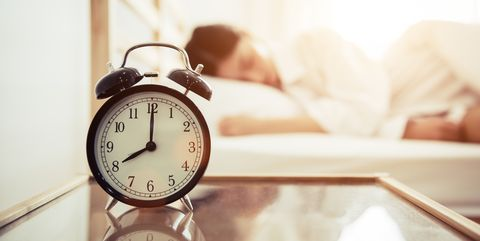 Close-Up Of Alarm Clock On Table By Woman Sleeping On Bed At Home