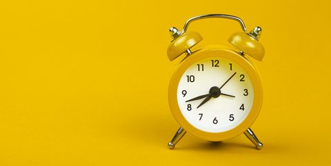 close up of alarm clock over yellow background