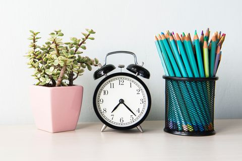 Close-Up Of Alarm Clock With Potted Plant And Pencils In Container On Table