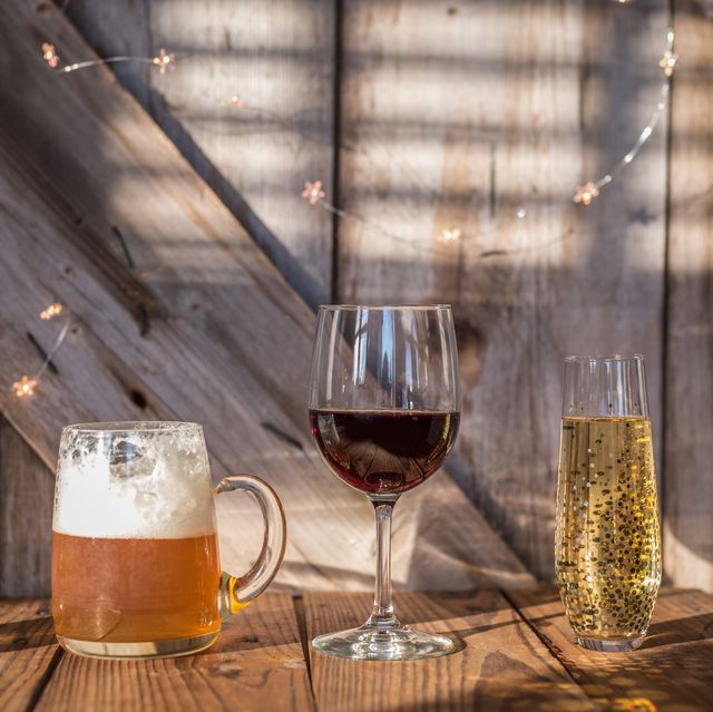 close up of alcohol in various glasses on wooden table