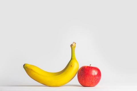close up of apple and banana against white background