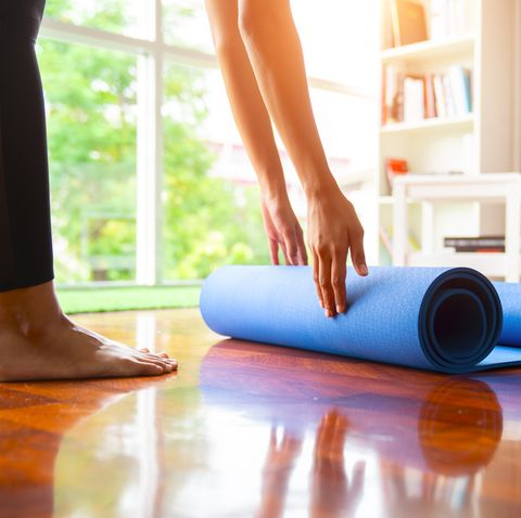 close up of attractive young woman folding blue yoga or fitness mat after working out at home in living room