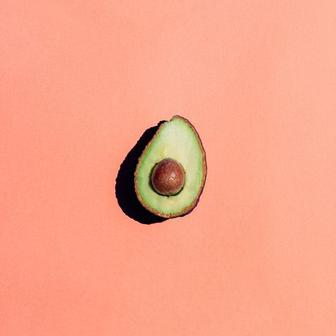 close up of avocado against pink background