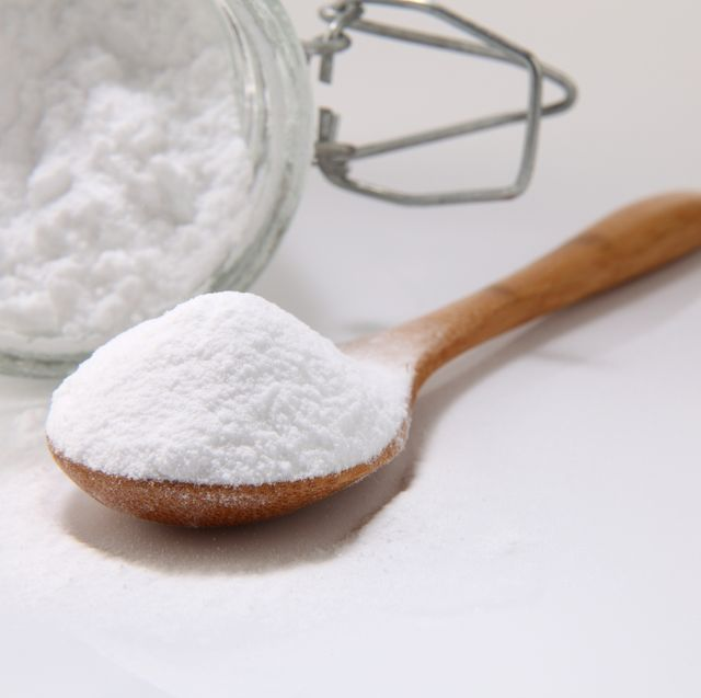 close up of baking soda in wooden spoon and jar on white background