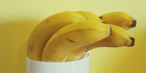 Close-Up Of Banana In White Container Against Yellow Wall