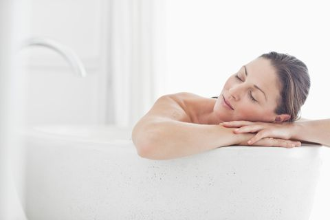 close up of beautiful mid adult woman relaxing in bathtub with eyes closed