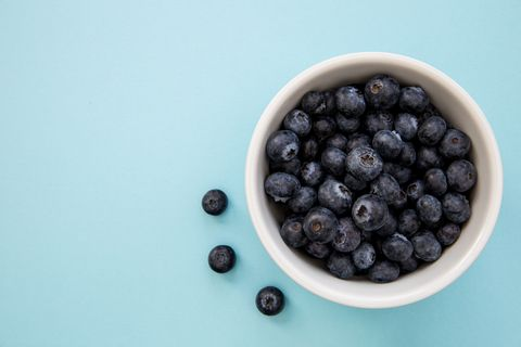 Close-Up Of Blueberries In Bowl On Blue Background