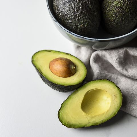 close up of bowl of avocados with one cut in half on white countertop