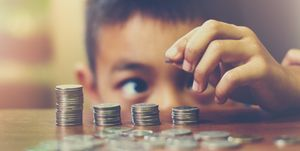 Close-Up Of Boy Stacking Coins On Table