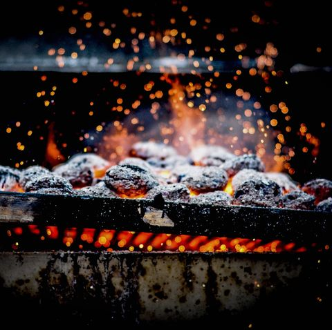close up of burning coal on metal grill