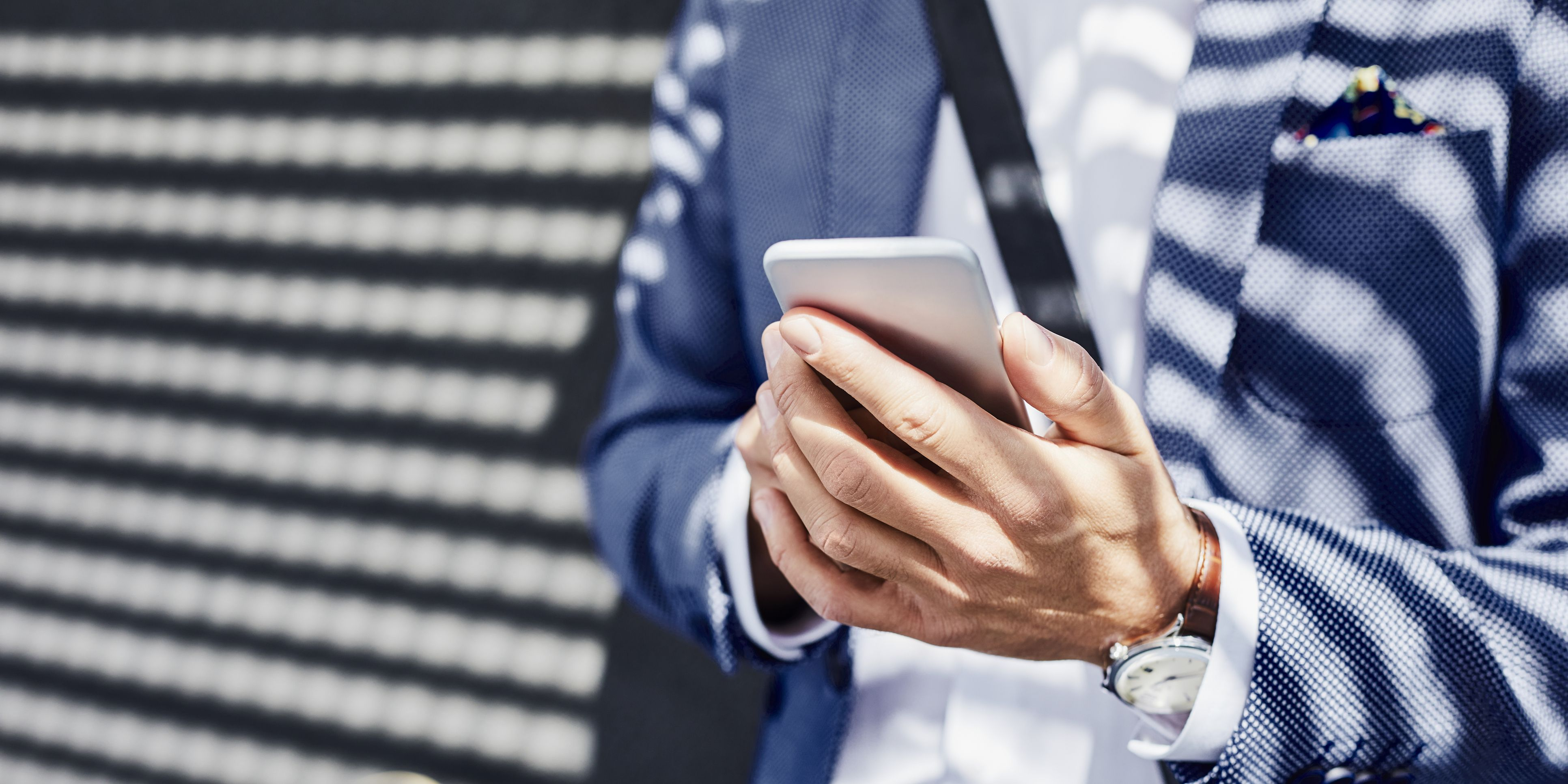 Close-up of businessman holding phone outdoors